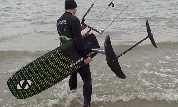kitesurfer loopt in het water met een hydrofoil