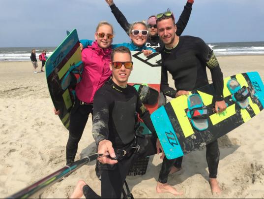 5 personen staaan met kitesurf wetsuit aan blij met de handen in de lucht