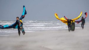 kitesurfers lopen door harde wind